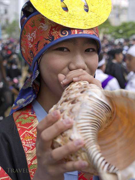 Girl with shell horn at Tug of War Festival, Okinawa