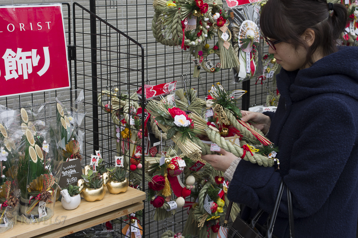 Japanese woman shopping for a New Years wreath, Tokyo, Japan