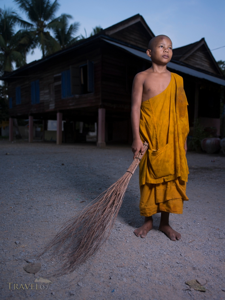 Young monk sweeping courtyard at dawn, Angkor Wat, Cambodia