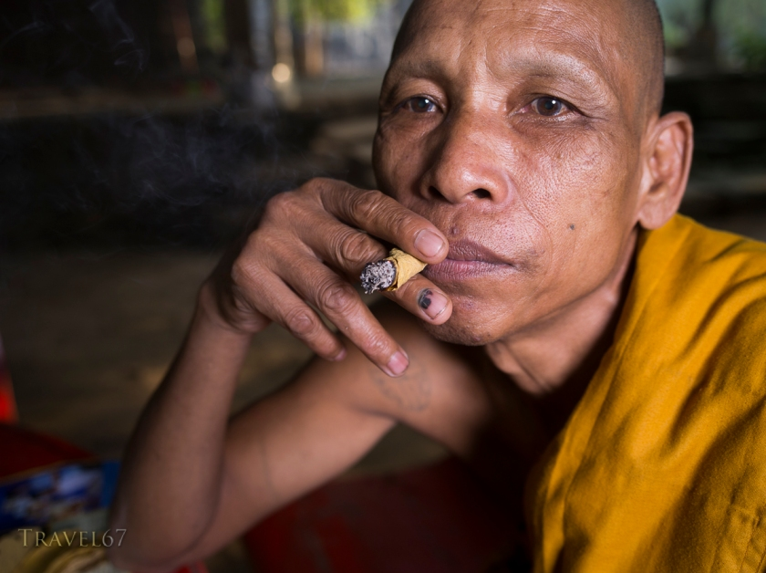 Cambodian Buddhist monk smoking a handrolled cigar made with sankai leaf.
