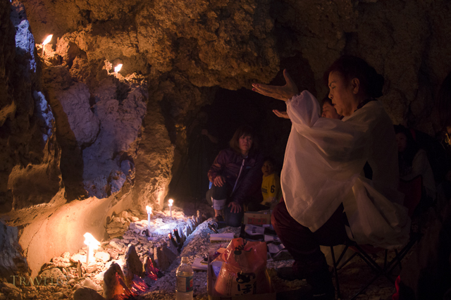 Yuta (priestess) Ayako Toguchi conducts prayers at sea cave called Sururu Gama on the coast of Kouri Island, Okinawa, Japan