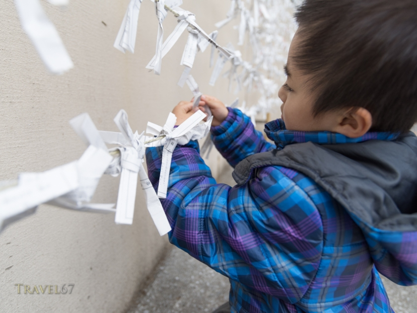 New Year Celebrations at Futenma Shrine, Okinawa, Japan. 1/1/2015. Child tying omikuji fortune paper to string.