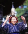 Elderly Okinawan lady dancing with a bottle of Awamori balanced on her head. Ryukyu Mura, Okinawa