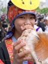 A young girl plays a traditional conch shell horn at the Eisa dance along Kokusai Street