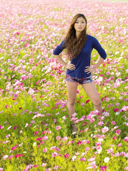 Okinawan girl in field of cosmos flowers.