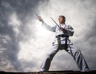 Yukio Kuniyoshi. Kaicho of Ryukyu Kobudo Hozon Shinko Kai. Training on Okinawa, Japan with manji sai.