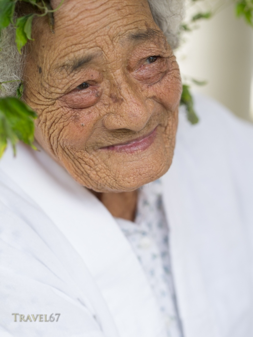 96 year old Kaneshi Fusae wearing wreath of ryukyu botanzuru at Unjami Festival on Kouri Island, Okinawa