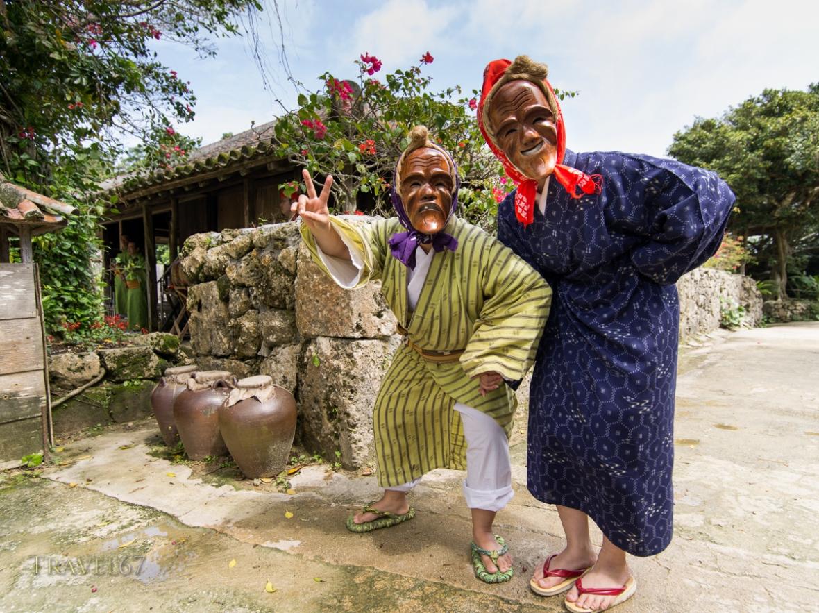Traditional Okinawan dancers wearing masks of smiling elderly people at Ryukyu Mura, Okinawa, Japan