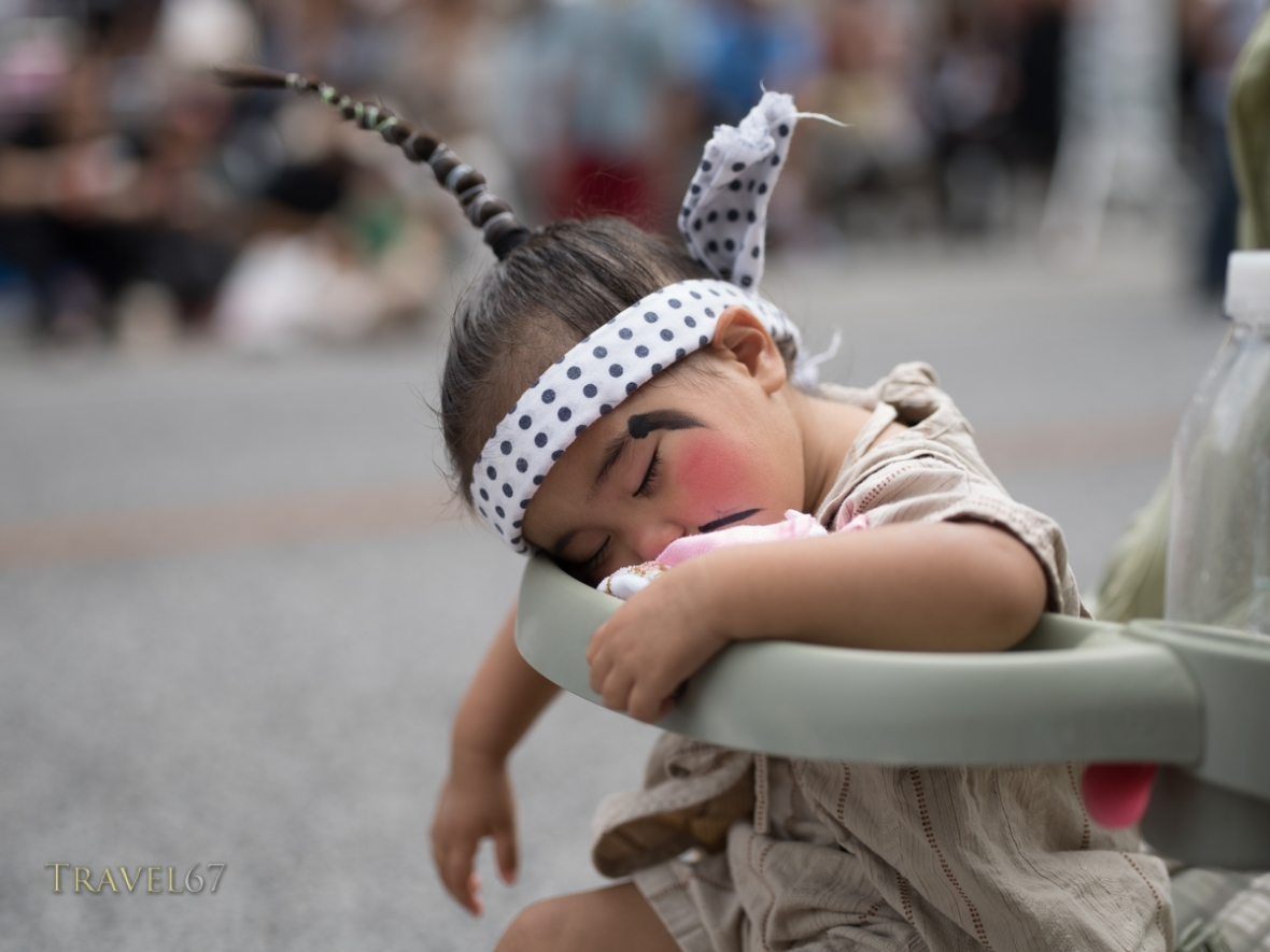 Young child in chondara costume sleeping through the Ryukyu Dynasty's procession at Kokusai Street, Naha.