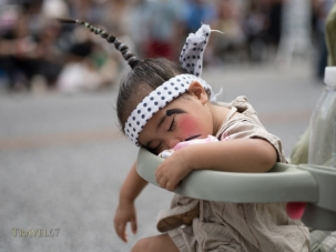 Young child in chondara costume sleeping through the Ryukyu Dynasty's procession at Kokusai Street, Naha.