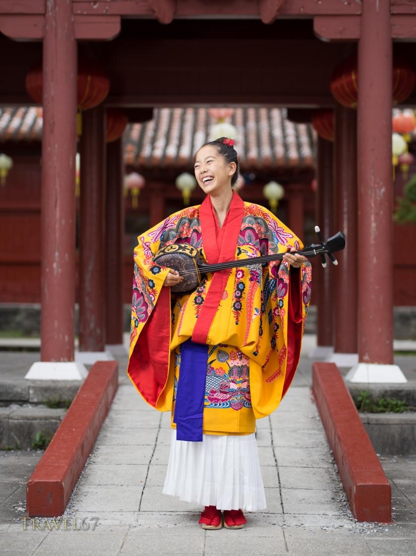 Okinawa musician Nayuta Hirano with sanshin (instrument) and traditional Okinawan ryuso kimono at Murasaki Mura, Yomitan, Okinawa