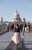 Woman walking across Millennium Bridge away from St. Paul's Cathedral, London, England.